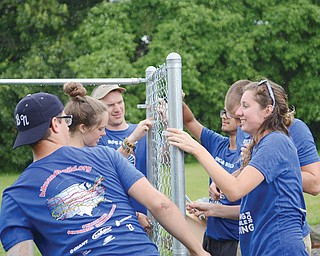 A group of young adults from Bike & Build puts together a fence at the Habitat for Humanity ReStore on Youngstown-Poland Road on Tuesday. Bike & Build is a nonprofit organization that organizes cross-country bicycle trips to benefit affordable housing groups.