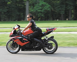 "Courtney Brown, whose nickname is ""Red,"" is vice president of Dangerous Curvez MC Inc. She rides a Suzuki GSXR 1000."