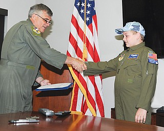 Col. Bill Phillips, left and Ethan Libert, right, shake hands Wednesday after Ethan was sworn in as an honorary second lieutenant as part of the 910th Airlift Wing's Pilot For A Day program.