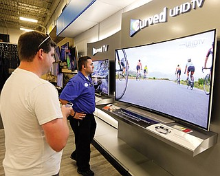 Jake Willis, center, home-theater supervisor at the Best Buy store in Greenwood, Ind., talks with customer Landon