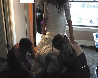 Lisa Plummer of Columbus, right, lifts up the dress while Rachel Nock of Canfield, left, helps her big sister Bridget Boysen of Seattle, slip into her wedding shoes. The wedding took place Sept. 14, 2013, in Seattle. Sent by Anne Nock of Canfield.
