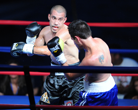 PITTSBURGH, PENNSYLVANIA - JULY 11, 2014: Jake Giuriceo follows through with a punch to the head of Travid Hartman during a welterweight bout Friday night at Rivers Casino. Giuriceo would win via 4th round TKO. (Photo by David Dermer/Youngstown Vindicator)