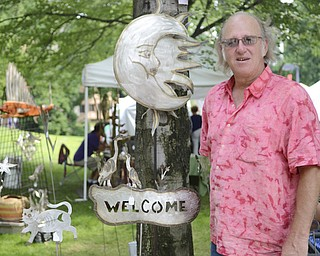 Katie Rickman | The Vindicator.Alex Stoll of Collins, Ohio, stands beside some of his stainless steel yard art at the Summer Festival of the Arts Saturday. Stoll has been selling his handcrafted items at the event, which takes place on the campus of Youngstown State University, for the past 13 years.