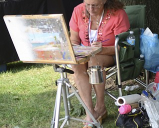 Katie Rickman | The Vindicator.Catherine Kendrick of Salineville paints beside her tent. Kendrick has been selling her wares at the festival, located on the campus of Youngstown State University, for the past four years.