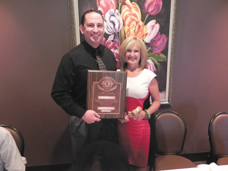 SPECIAL TO THE VINDICATOR Youngstown Lions Club new President Adam Costello presented retiring President Nancy Cuffle with a plaque, pin and gavel at a recent luncheon at the Upstairs Lounge in Austintown. Costello also received a gavel and pin from Cuffle. New officers and board members were installed during a candlelight ceremony.