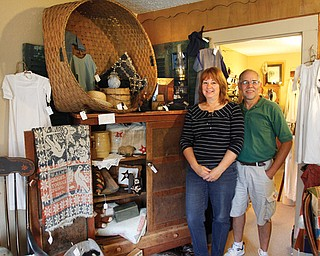 Joe and Linda Matulek stand near the wool basket and pie safe inside their antique shop, Cracked Crock in  Canfield. The shop has a variety of items from furniture to antique christening gowns.
