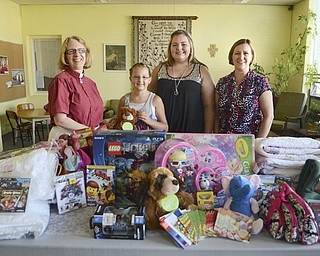 Mariah Leskovac, 10, second from left, and her sister, Destiny, 13, third from left, created Mariah's Destiny to collect donations of new items such as toys and games for sick children. The idea evolved from Mariah's cancer diagnosis, treatment and recovery. The sisters received donations at their church, Trinity Lutheran in Niles, where the Rev. Dee Emmert, left, is pastor. Accepting donations is Sue Neitz, right, stem-cell transplant coordinator at Akron Children's Hospital.