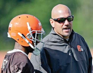 Browns head coach Mike Pettine talks with wide receiver Chandler Jones during practice at the team's training camp in Berea.