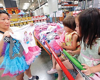 Carry Johnson, left, shows dresses to her daughters Zoey, center, and Payton while they shop at a Costco in Plano, Texas. The private Conference Board reported Tuesday that consumers are more confident about the economy than they have been in nearly seven years.
