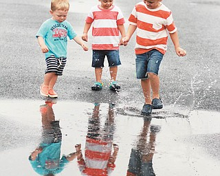 Sam Manning, 4; Leo Manning, 2; and Owen Holt, 1 1/2, are ready to step right in the puddle at Bethany Beach.