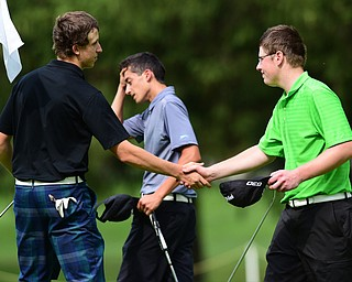 HUBBARD, OHIO - JUNE 26, 2015: Nick Braydich of Mooney shales hands with Zach Jacobson of Poland after fining their round of golf while Anthony Graziano of Girard reacts behind them on the 18th hole Friday afternoon at Pine Lakes during a Vindy Greatest Golfer qualifying Tournament. DAVID DERMER | THE VINDICATOR