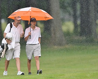 Jeff Lange | The Vindicator  JULY 26, 2015 - Anthony Granziano of Girard (right) and personal coach John Perry of Houston, Texas walk the course in a downpour during Sunday afternoon's Greatest Golfer of the Valley Junior championship held at Avalon Lakes Golf & Country Club in Howland.