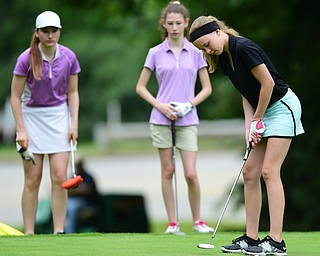 HERMITAGE, PENNSYLVANIA - JUNE 19, 2015: Jenna Jacobson of Poland follows through on her putt on the 13th hole while Hannah Keffler and Madison Dailey watch on Friday morning at Tam O' Shanter during the Vindy Greatest Golfer junior qualifier. DAVID DERMER | THE VINDICATOR