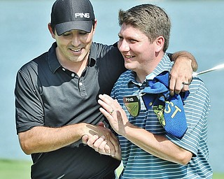 Jeff Lange | The Vindicator  AUGUST 23, 2015 - Upon winning the Pete Mollica's Open Division of the Greatest Golfer tournament, Jonah Karzmer of Poland (right) is congratulated with a hug and a handshake from competitor Scott Porter of Poland, Sunday afternoon at the Lake Club in Poland. Karzmer won by five strokes with a final score of 213.