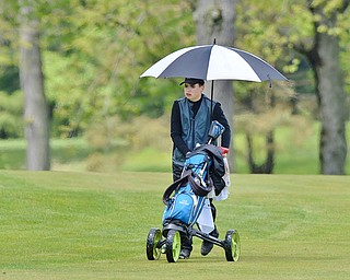 Jeff Lange | The Vindicator  SUN, MAY 15, 2016 - Boardman's Cole Christman walks down the fairway under the shade of an umbrella during Sunday's Greatest Golfer of the Valley junior event at Avalon Lakes at Squaw Creek.