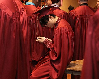 Nikos Frazier | The Vindicator..A Cardinal Mooney High School student looks at his phone before lining up in Stambaugh Auditorium to receive his diploma.