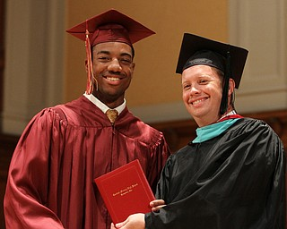 Nikos Frazier | The Vindicator..Aaron Woodberry receives his Cardinal Mooney High School diploma from Principal Mark Vollmer.