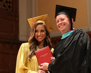 Nikos Frazier | The Vindicator..Cia Lyras receives her Cardinal Mooney High School diploma from Principal Mark Vollmer.