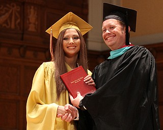 Nikos Frazier | The Vindicator..Lexy Herman receives her Cardinal Mooney High School diploma from Principal Mark Vollmer.