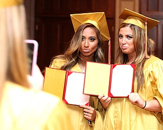 Nikos Frazier | The Vindicator..Cia Lyras(left) poses with Julie Cook(right) with empty diplomas after graduating from Cardinal Mooney High School on Sunday, May 29, 2016.
