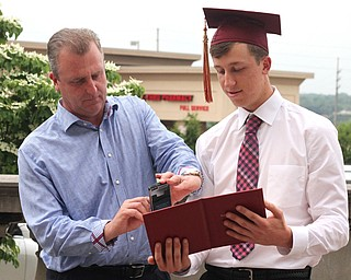 Nikos Frazier | The Vindicator..Mark Braydich(left) takes a picture of his son, Nick Braydich's diploma after Nick graduated from Cardinal Mooney High School.