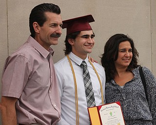 Nikos Frazier | The Vindicator..Nicholas Koken(center) poses with his parents outside of Stambaugh Auditorium after receiving his diploma from Cardinal Mooney High School.