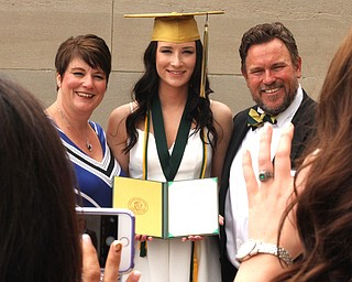 Nikos Frazier | The Vindicator..Erica Lehn(center) poses with her parents, Alexandria Rossetti(left) and William Lehn(right) outside of Stambaugh Auditorium after graduation from Ursline High School.