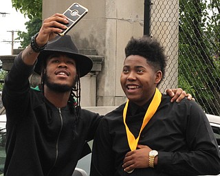 Nikos Frazier | The Vindicator..Daekwaun Thomas(left) and Malik Everson snap a selfie outside of Stambaugh Auditorium after Everson graduated from Ursline High School.