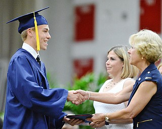 Jeff Lange | The Vindicator  SUN, MAY 29, 2016 - Andrew Green (left) shakes hands with Kathy Mock as he receives his diploma during Sunday's commencement at Austintown Fitch High School.