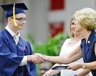 Jeff Lange | The Vindicator  SUN, MAY 29, 2016 - Van Blevins shakes hands with Kathy Mock as he receives his diploma during Sunday's commencement at Austintown Fitch High School.