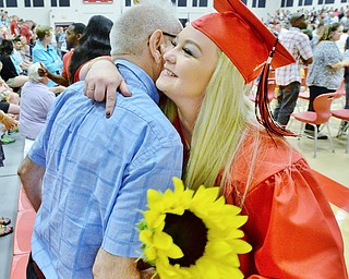 Jeff Lange | The Vindicator  SUN, MAY 29, 2016 - Taylor Schlatter (facing) hugs Ralph Funaro of Girard after Sunday's commencement at Girard High School. Schlatter has known Ralph since childhood when his wife, Joan, babysat her.
