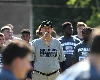 Nikos Frazier | The Vindicator..Jim Harbaugh, Michigan  Football Head Coach, watches as players run during the Warren Harding Elite Camp.