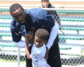 Nikos Frazier | The Vindicator..Mario Manningham(top) plays with his son, Mario Manningham Jr., 5, during the Warren Harding Elite Camp. Manningham, originally from Warren, played for Harbaugh and the 49ers in 2012 and 2013 as well as Michigan State in college.