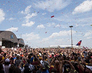 Confetti is sprayed over the crowd as the Cleveland Cavaliers arrive at the airport after winning Game 7 of basketball's NBA Finals against the Golden State Warriors the previous night, Monday, June 20, 2016, in Cleveland. Cleveland won 93-89. (AP Photo/John Minchillo)