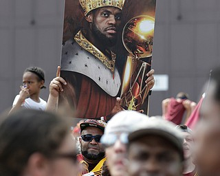 A man holds up a photo of Cleveland Cavaliers' LeBron James as he waits the arrival of the team in Cleveland, Monday, June 20, 2016. Lebron James came home with the trophy he promised, and the championship Cleveland has coveted for 52 years. The NBA superstar, born and raised in nearby Akron, stepped off a plane Monday and hoisted the shiny Larry O'Brien Trophy as more than 10,000 fans celebrated the city's first title since 1964. (AP Photo/Tony Dejak)