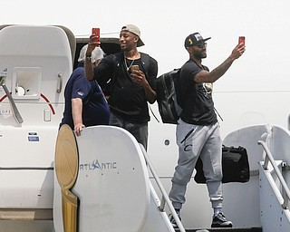 NBA champion Cleveland Cavaliers' Jordan McRae, right, and Iman Shumpert, left, take photos of a cheering crowd as they arrive at the airport Monday, June 20, 2016, in Cleveland. (AP Photo/John Minchillo)