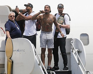 Cleveland Cavaliers' Tristan Thompson, second from left, J.R. Smith, center, and Kevin Love, right, celebrate as they arrive at the airport after winning Game 7 of basketball's NBA Finals against the Golden State Warriors the previous night, Monday, June 20, 2016, in Cleveland. Cleveland won 93-89. (AP Photo/John Minchillo)