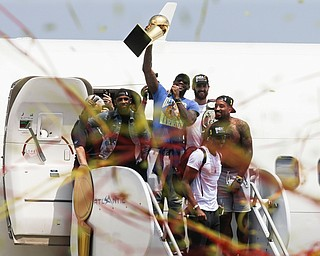 NBA champion Cleveland Cavaliers Lebron James, center, holds up the NBA championship trophy alongside teammates Kyrie Irving, left, Kevin Love, rear right, J.R. Smith, right, and Tristan Thompson, front, as they arrive at the airport Monday, June 20, 2016, in Cleveland.  (AP Photo/John Minchillo)