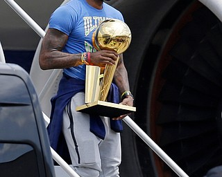 Cleveland Cavaliers' LeBron James carries The Larry O'Brien NBA Championship Trophy after arriving in Cleveland, Monday, June 20, 2016. (AP Photo/Tony Dejak)
