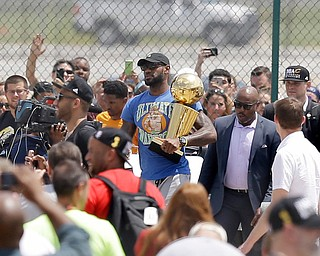 Cleveland Cavaliers' LeBron James carries the NBA Championship trophy after arriving in Cleveland, Monday, June 20, 2016. (AP Photo/Tony Dejak)