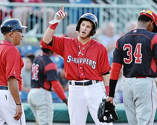 Jeff Lange | The Vindicator  SAT, JUN 25, 2016 - Scrappers Alexis Pantoja (center) looks back to the dugout in celebration of his 2 RBI triple to right field in the fourth inning as manager Edwin Rodriguez (52) comes to congratulate him in the fourth inning of a baseball game against Batavia at Eastwood Field on Saturday.