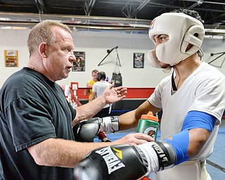 Jeff Lange | The Vindicator  SAT, JUL 9, 2016 - John Loew of South Side Boxing (left) coaches Popo Salinas in between rounds of a sparring match during training at the gym on Market Street on Saturday, July 9, 2016.