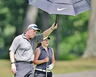 Jeff Lange | The Vindicator  FRI, JUL 22, 2016 - Ken Cerimele of Canfield (left) holds an umbrella over his daughter Gillian as they survey the No. 8 fairway during Friday's Greatest Golfer of the Valley Junior finals held at Avalon at Squaw Creek.