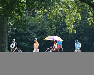 Jeff Lange | The Vindicator  FRI, JUL 22, 2016 - A group of golfers including Cade Kreps (in orange) and Anthony Graziano (right) walk down the No. 10 fairway in a drizzling rain during Friday's Greatest Golfer of the Valley Junior finals held at Squaw Creek.