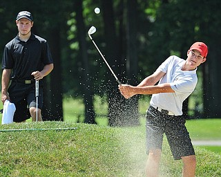 Jeff Lange | The Vindicator  SAT, JULY 23, 2016 - Cade Kreps of Boardman (right) plays his ball from the No. 8 bunker as his caddy Michael Melewski looks on from behind during the second round of the Greatest Golfer of the Valley Junior finals held at Avalon Lakes in Vienna Saturday afternoon.