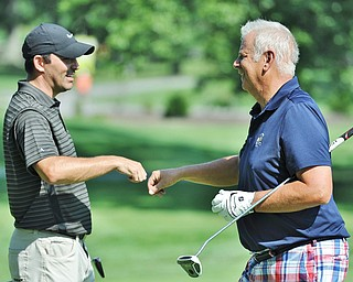 Jeff Lange | The Vindicator  FRI, AUG 19, 2016 - Glenn Milton (right) is congratulated by Scott Porter after finishing No. 18 on the North Course at Mill Creek Golf Course during the first round of the 2016 Farmers Bank Greatest Golfer of the Valley competition on Friday, Aug. 19, 2016.