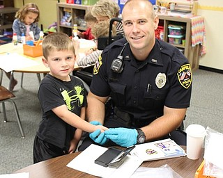 Neighbors | Abby Slanker.Canfield Police Department School Resource Officer Steve Garstka fingerprinted a Hilltop Elementary School kindergartner for the Child Safety Fingerprint ID Kits the department provided for kindergartners Sept. 28.
