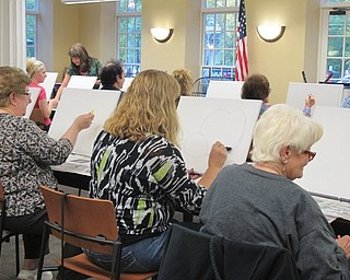 Neighbors | Alexis Bartolomucci.Guests at the Poland library painting event on Oct. 3 worked on sketching out their pumpkins before they painted them.