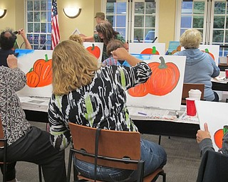 Neighbors | Alexis Bartolomucci.People who attended the painting event at the Poland library on Oct. 3 worked on painting the sky after they finished painting their pumpkins.