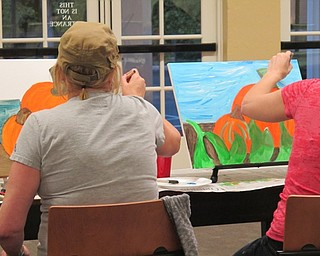 Neighbors | Alexis Bartolomucci.Two guests at the Poland library worked on finishing up their pumpkin paintings during the paint event on Oct. 3.